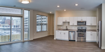 View of the kitchen and Juliette balcony with sliding glass doors, from the living area in apartment 1-B.
