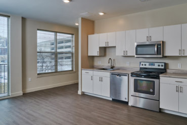 Adjacent to the kitchen in apartment 1-B is a Juliette balcony with sliding glass doors.