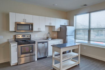 The kitchen in apartment 1-A has neutral laminate countertops, a moveable island, and stainless steel appliances.