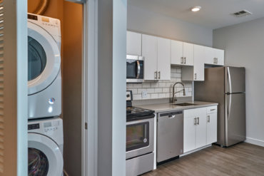 Bright kitchen in apartment 1-F with Corian countertops, tile backsplash, stainless steel appliances, and an adjacent laundry room with a stackable washer and dryer.