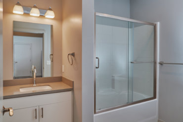 Full bath with tub and sliding glass door in apartment 1-F.