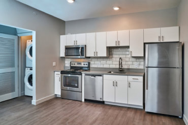 Bright kitchen in apartment 1-F with Corian countertops, tile backsplash, and stainless steel appliances.