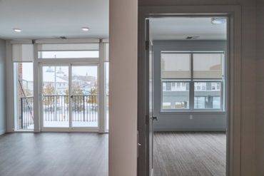 View of the spacious living area, balcony with sliding glass doors, and one of two bedrooms in apartment 2-B.