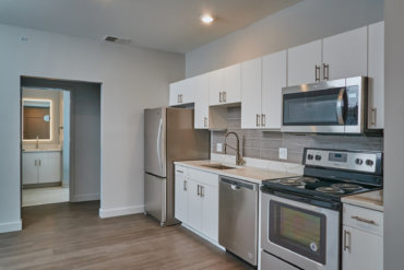 Modern kitchen in apartment 2-B with quartz countertops, tile backsplash, under-cabinet lighting, and stainless steel appliances.