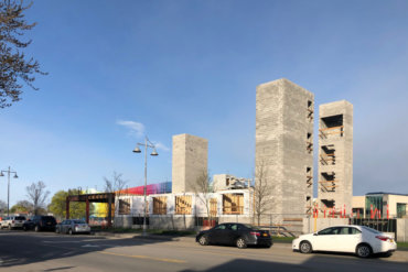 A look southwest, across S. Union Street, towards Building D, with the Neighborhood of Play parking garage in the background.