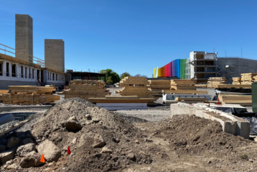 View from the north side of Building D, looking south towards the colorful Neighborhood of Play parking garage and the future site of the Hampton Inn.