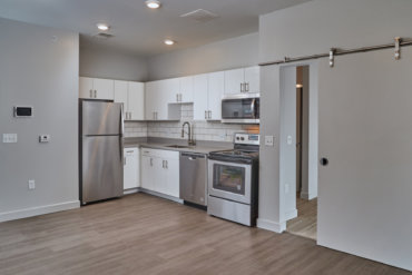 The kitchen in our studio apartment features Corian countertops, a tile backsplash, stainless steel appliances, and a barn door, which separates the living areas from the bedroom and bathroom.