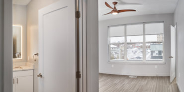 Hallway view into one of two full baths and bedrooms in our 2-bedroom townhome, with walk-in closet and UV shades.