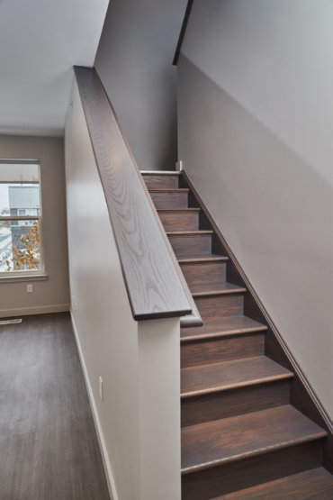 First-floor staircase in our 2-bedroom townhome, located adjacent to the living and dining areas.
