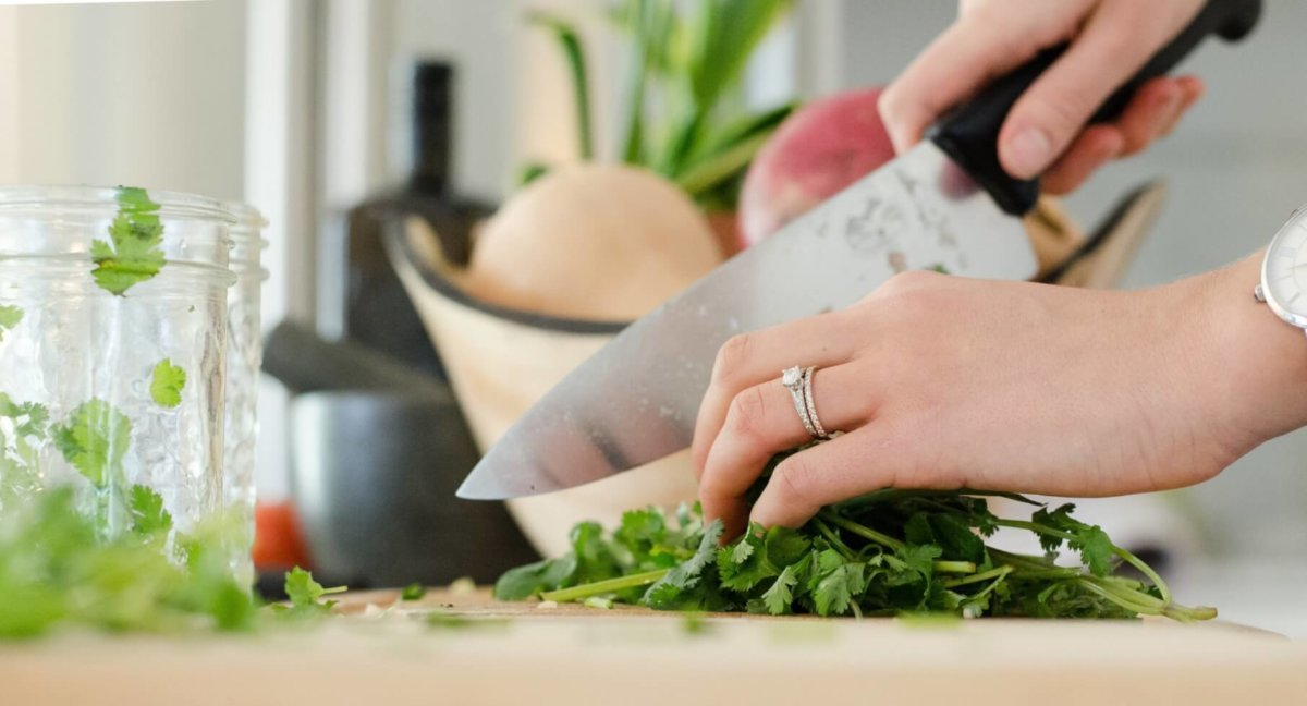 Woman chopping herbs with a chef's knife