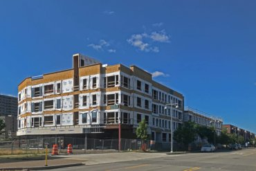 Construction on Building D as seen from S. Union Street looking north. The open area on the ground floor will be retail space.