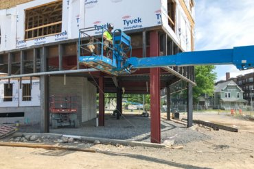 A welder working on the first-floor retail space of Building D.