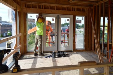 Workers install glass doors in a second-floor apartment (unit 2A) in Building D.