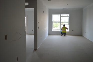 Unit 1C in Building D starting to come together after flooring has been poured and drywall and primer have been added.