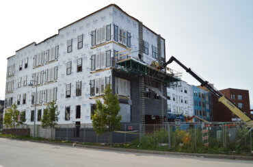 A view of the northwest side of Building D, where windows and doors are being installed.