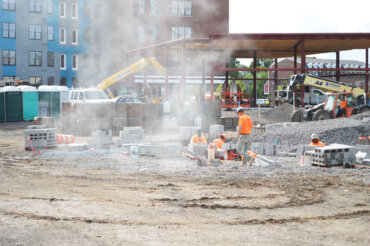 The foundation for Building B is underway in the foreground, while beam work continues on Building C behind it. Building D stands 4-floors tall in the background.