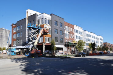 A north-facing view of Building D along S. Union St. as work continues on the exterior siding.