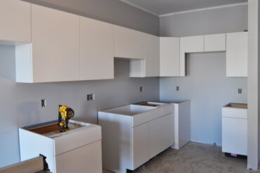 Kitchen cabinets being installed in a one-bedroom apartment (1-C) in Building D.