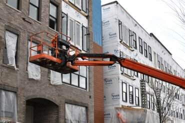 Building D along S. Union St. where construction workers are completing the brickwork.