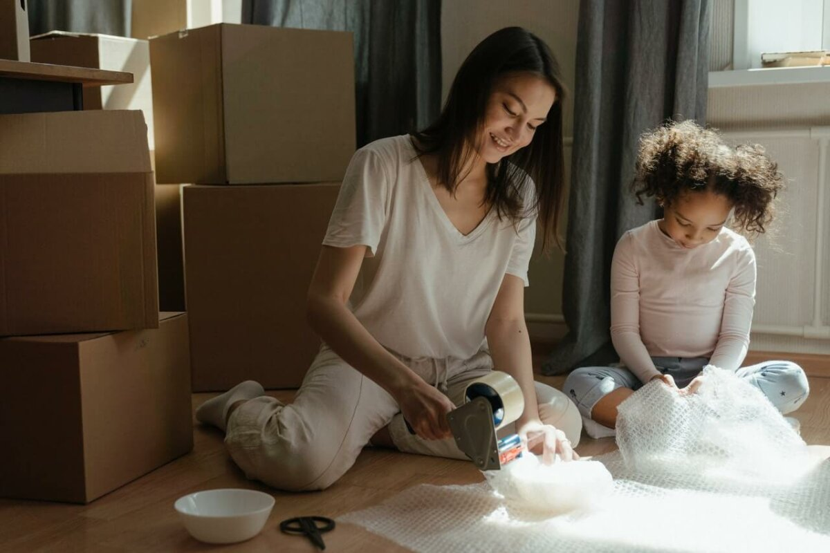 Woman and young girl using bubble wrap to pack for a move