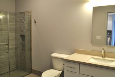 Work is nearing completion on the bathroom of this two-bedroom apartment (unit 2C) in Building D. It features a recessed floor drain and beautiful tile work in the walk-in shower.