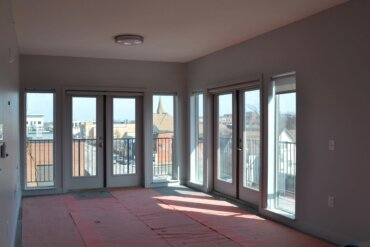A view of South Union Street from the living room of a two-bedroom apartment (unit 2D) in Building D. This corner unit features a wrap-around balcony accessible from two sets of double doors.