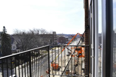 Construction workers use a skylift to work on the facade of Building D in this view from the balcony of a third-floor apartment (unit 2D).