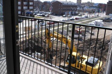 A view of South Union Street and a bright yellow excavator from the balcony of a one-bedroom apartment (unit 1D) in Building D.