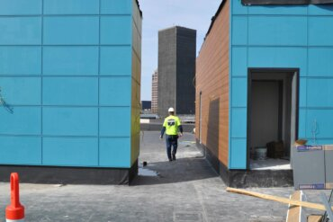 A construction worker walks between two landings on what will be the rooftop deck of Building D.