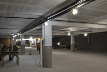 Workers in the underground parking garage of Building D.