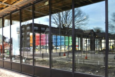 A view of the all-glass exterior of the first-floor retail space in Building D. The colorful new Neighborhood of Play parking garage is reflected in the glass.