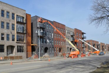 Workers use skylifts to put the finishing touches on the exterior of Building D along South Union Street.