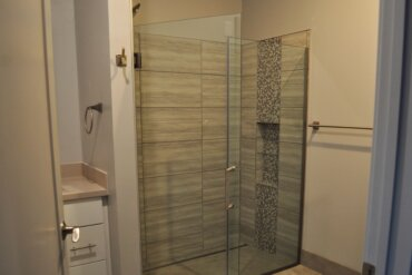 This beautiful tile shower with built-in shelf is one of the two full baths in Unit 2D.