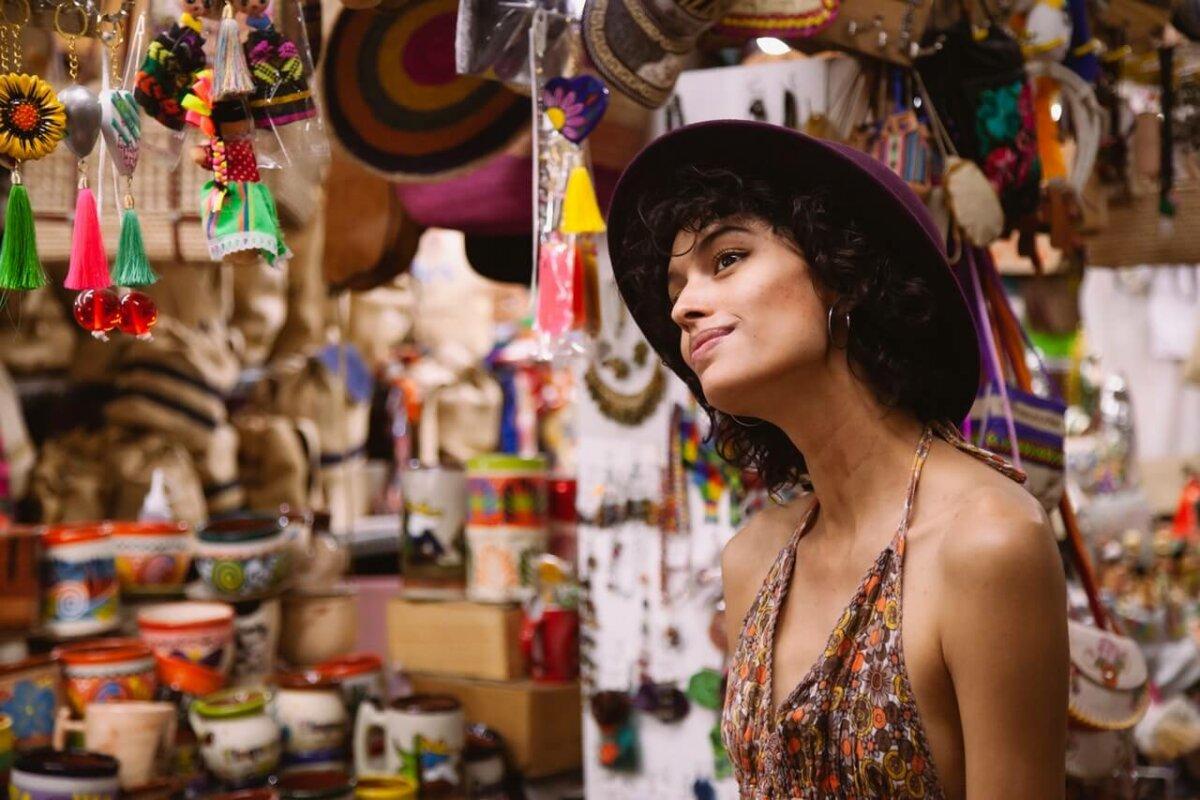 Woman looking at souvenirs in a shop. Image credit: los Muertos Crew