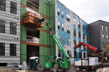 A skyjack lifts a shipment of cabinetry that will be installed in Building B.