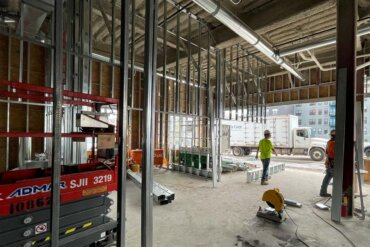 Work on the interior framing of the VIDA leasing office in Building B.