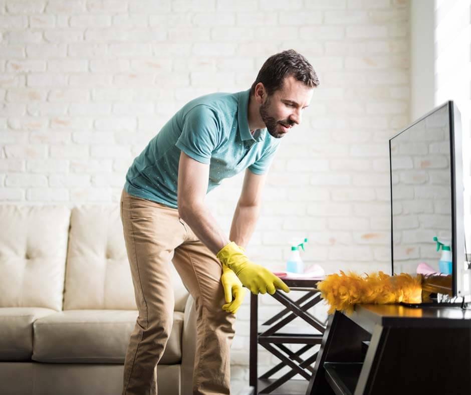 Man dusting a television stand. Photo credit Antonio Diaz