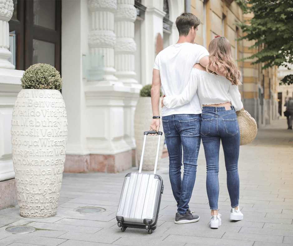 Two people walking down the sidewalk pulling a small suitcase. Photo credit: Andrea Piacquadio